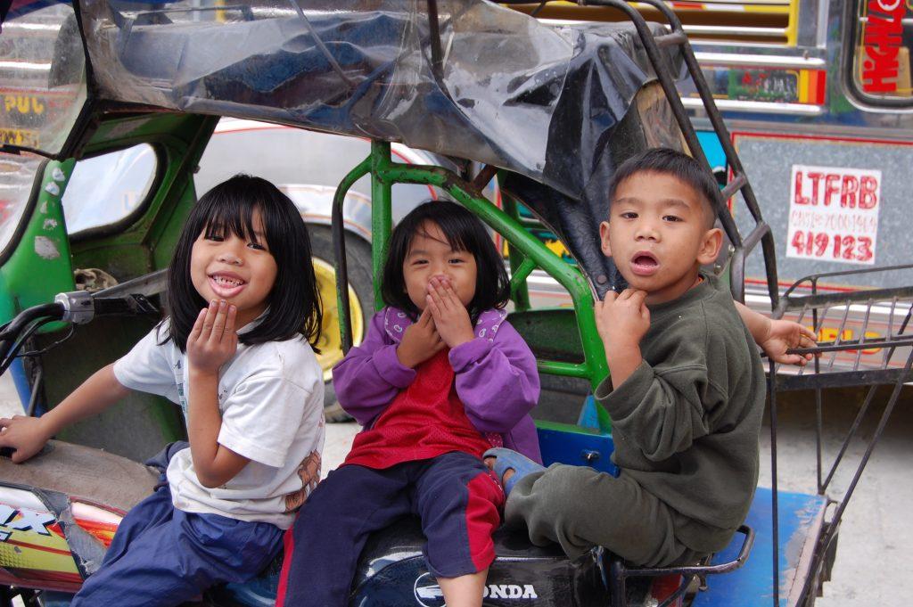Herumalbernde Ifugao-Kinder auf einem Tricycle...