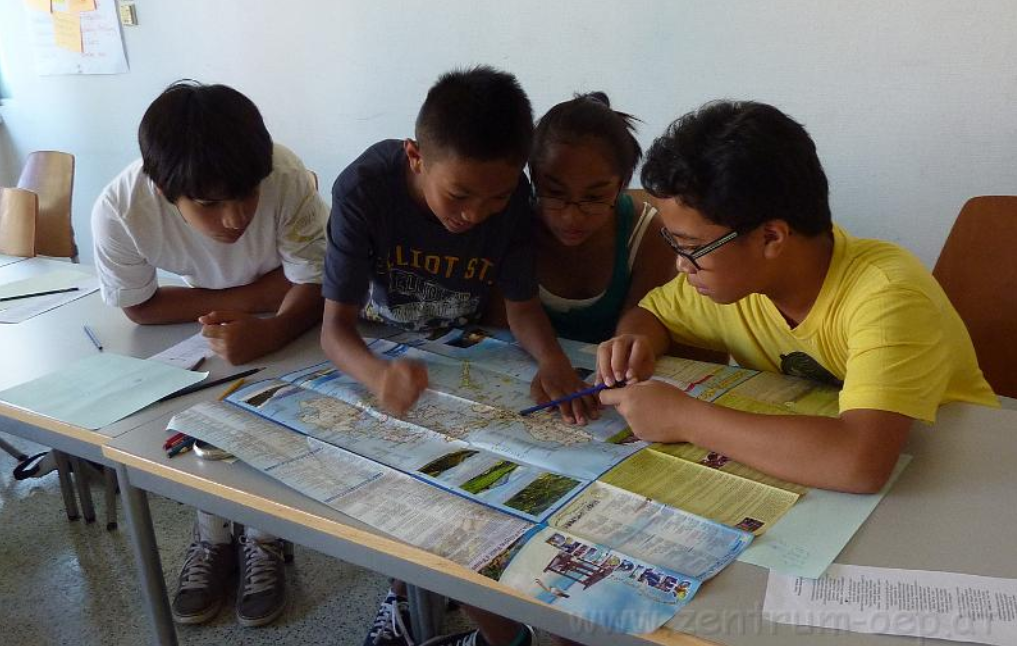 Kinder beugen sich über eine Landkarte der Philippinen