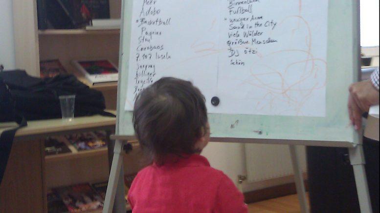 Junges Kind schaut eine Tafel mit österreichischen und philippinischen Wörtern an - Schule in der Botschaft 2013