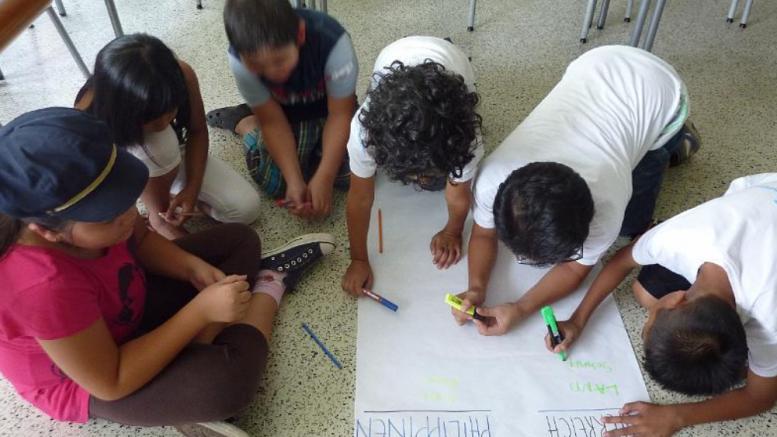 Kinder hocken über einem Fragebogen und suchen nach Unterschiede zwischen den Philippinen und Österreich